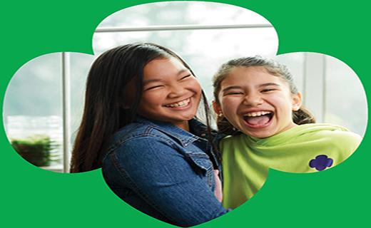 Two girls smiling inside a Girl Scouts logo